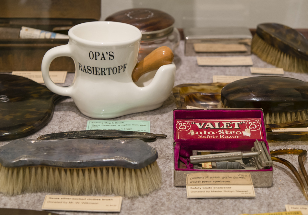 A collection of shaving paraphernalia, including Clothes brush, Safety blade sharpener and Shaving mug & brush.