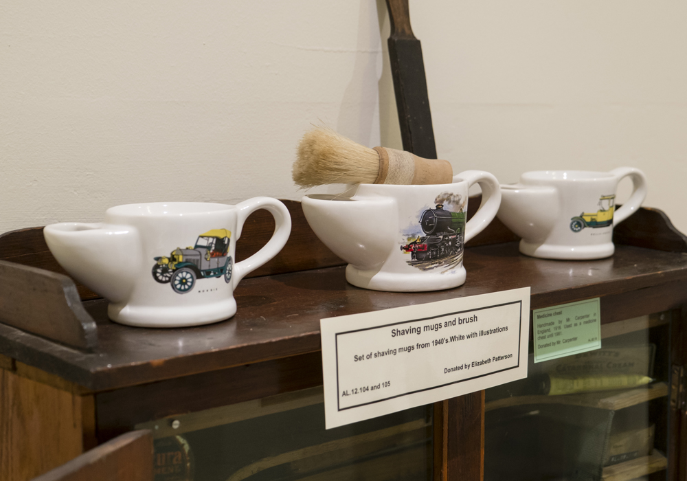 Shaving mugs and brush, set of shaving mugs from 1940's. White with illustrations. ~ Donated by Elizabeth Patterson.