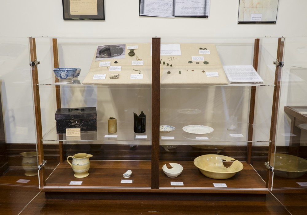 Various artifacts from the Peel Town Archaeology Project, including sewing artifacts, crockery and a Tin Cash Box.