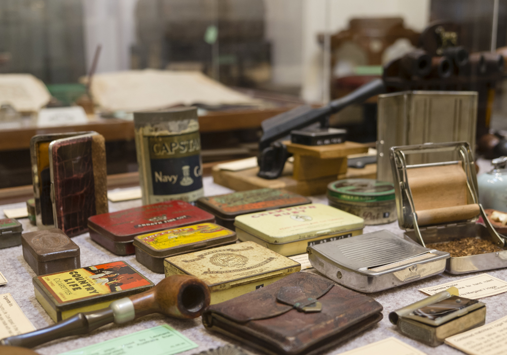 A range of smoking paraphernalia, including Tobacco tins, Match cases, Cigarette rollers and Pipes.