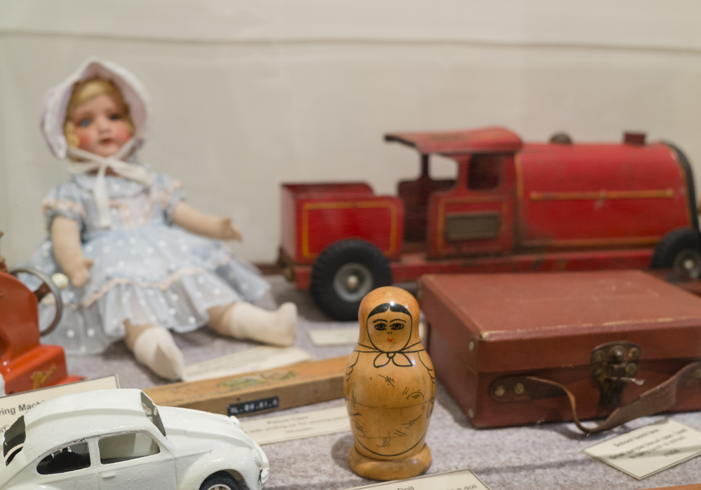 A range of children's toys including a Babushka Doll c.1962, School Lunch Box c.1928 and Toy Train c.1930-1940.