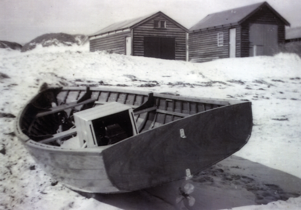 Boatsheds and small boat in the sand dunes at Coogee Beach. Boatsheds destroyed by winter storms in 1964.